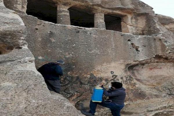 پاک سازی دیوارنوشته های دخمه سنگی فقره قا مهاباد
